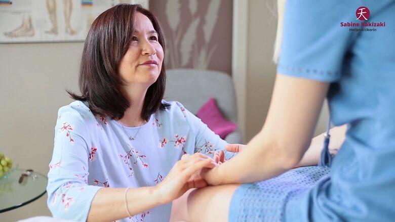 Heilpraktikerin kniet vor einer Patientin und macht Pulsdiagnose