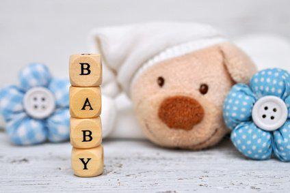 Baby und Holzwürfel mit Buchstaben bilden das Wort Baby