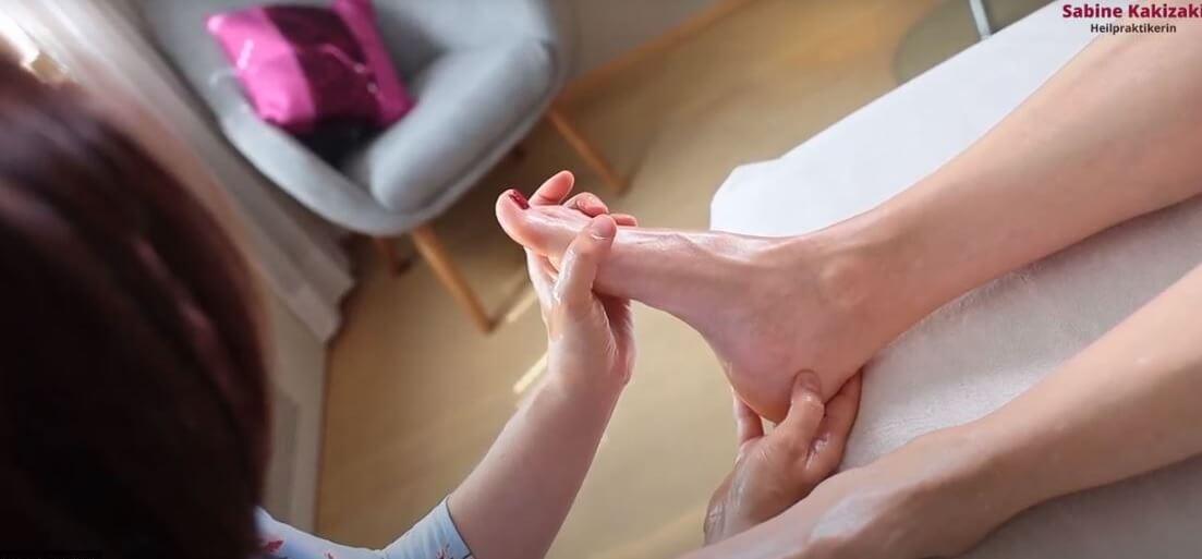 Heilpraktikerin massiert einer Patientin die Fußreflexzonen