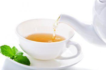 Eingießen einer Tasse Kräutertee, der in der TCM gesundheitsfördernd ist